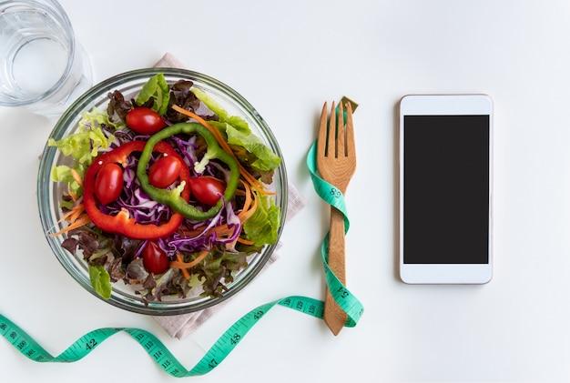 Salada fresca com fita métrica e smartphone de tela vazia
