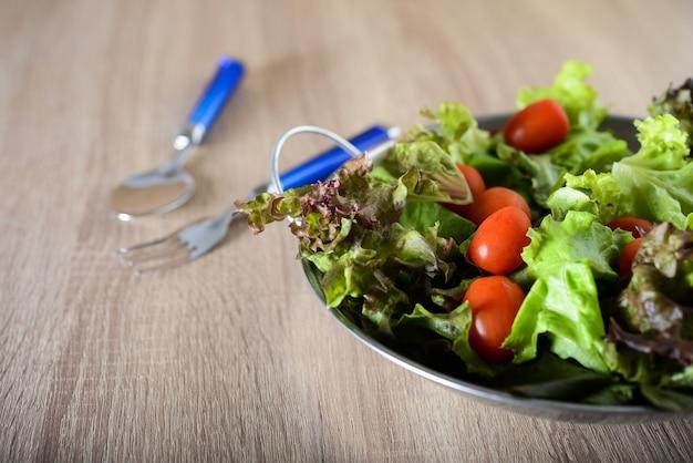 Salada fresca com legumes e verduras na mesa de madeira. conceito de alimentos saudáveis.