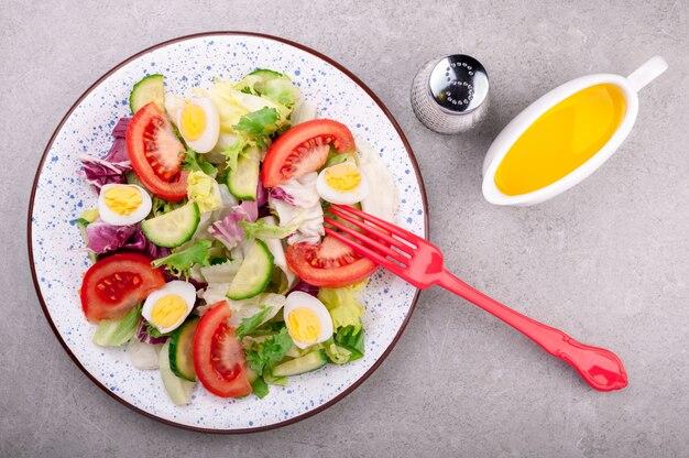 Salada fresca com legumes tomates, pepinos, folhas de salada de mistura, ovos e azeite.