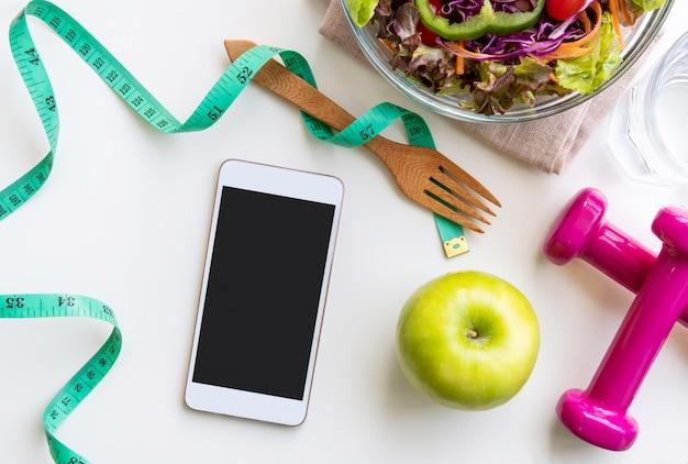 Salada fresca com maçã verde, haltere, fita métrica e smartphone de tela vazia