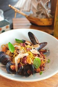 Salada fresca com mexilhões em uma mesa de madeira.