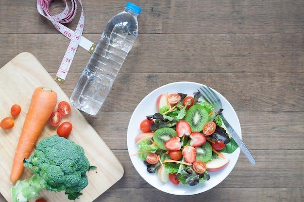 Salada fresca com morangos, kiwi, tomates e maçãs com garrafa de água, conceito de dieta e fitness