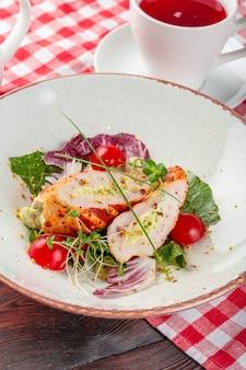 Salada fresca com peito de frango, rúcula e tomate em um prato