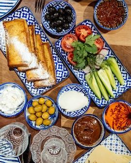 Salada fresca com pepinos, ervas e tomates, servidos com torradas e azeitonas pretas em cima da mesa