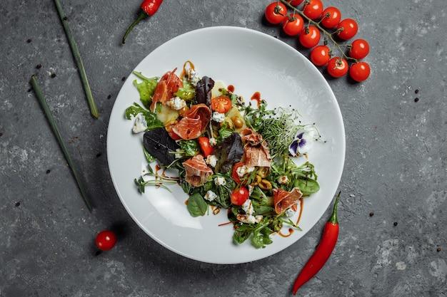 Salada fresca com presunto e pêra em um fundo cinza escuro