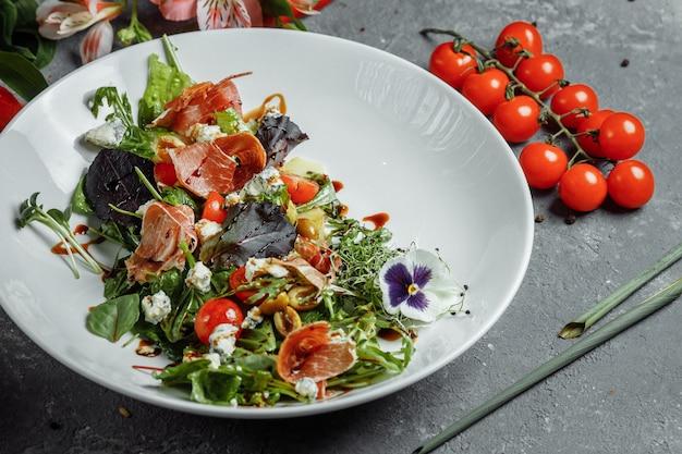 Salada fresca com presunto e pêra em uma mesa cinza escura. salada de jamon, mix para salada, espinafre, pêra, tomate cereja, dor blue, alcaparras e molho de vinagre bianco.
