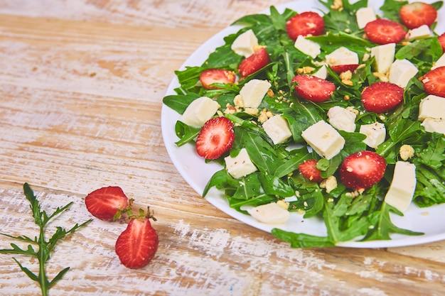 Salada fresca com rúcula, morangos, queijo feta e nozes.