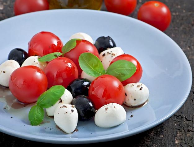 Salada fresca com tomate cereja, manjericão, mussarela e azeitonas pretas.