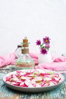 Salada fresca das partes de rabanete e aneto em uma placa em uma tabela de madeira. petisco pronto para uma dieta