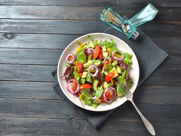 Salada fresca de abacate com tomate cereja, cebola roxa, folhas de beterraba rúcula, pimentão amarelo sobre o fundo preto de madeira. conceito de comida saudável. comida vegana.