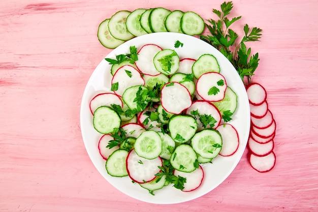 Salada fresca de pepino e rabanete em fundo rosa