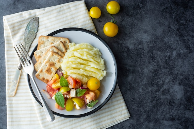 Salada fresca de tomate e purê de batatas em um prato. comida saudável de verão.