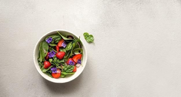 Salada fresca de verão de espinafre e morango e flores comestíveis