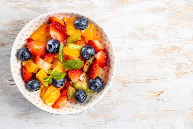 Salada fresca de verão de várias frutas e bagas. kiwi, laranja, morango e mirtilo em um prato decorado com hortelã