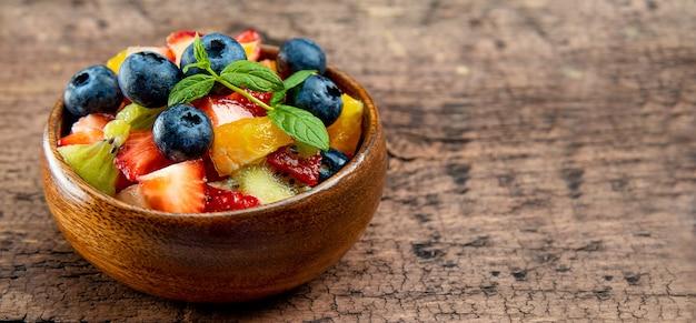 Salada fresca de verão de várias frutas e bagas. kiwi, laranja, morango e mirtilo em uma tigela de madeira decorada com hortelã
