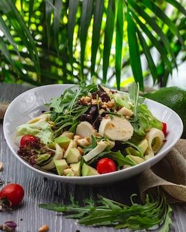 Salada fresca de vista frontal com rúcula abacate e tomate