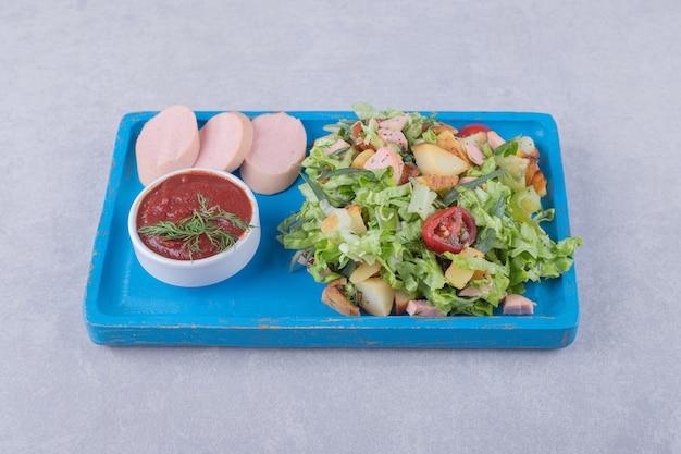 Salada fresca e salsichas cozidas na placa azul.