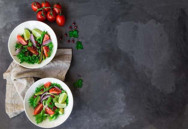 Salada fresca e saudável com tomate, abacate e romã em tigelas em concreto cinza. vista do topo.