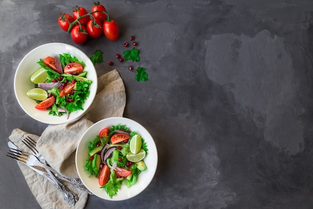 Salada fresca e saudável com tomate, abacate e romã em tigelas em concreto cinza
