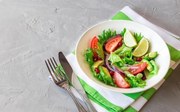 Salada fresca e saudável com tomate, abacate e romã em uma tigela sobre concreto leve.