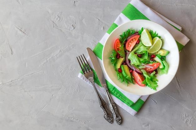 Salada fresca e saudável com tomate, abacate e romã em uma tigela sobre fundo claro de concreto
