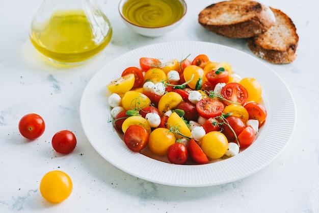 Salada fresca e saudável com tomate cereja, mussarela e azeite de oliva