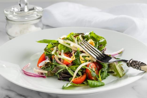 Salada fresca em prato branco de frente