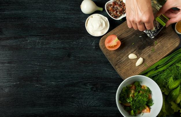 Salada fresca em um prato em uma superfície escura. alho, tomate, pepino, endro e cebola em um prato de superfície escura.