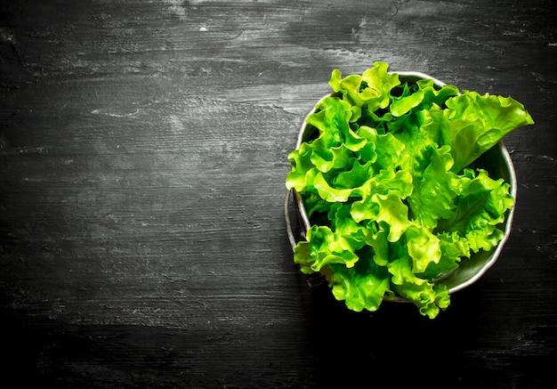 Salada fresca em uma panela na mesa de madeira preta