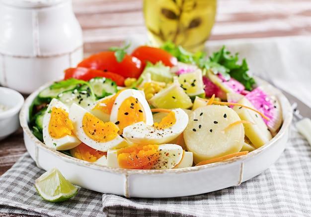 Salada fresca. tigela de buda vegetariano. tigela com batata cozida, pepino, tomate, rabanete melancia, alface, rúcula, milho e ovo cozido. comida saudável.