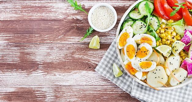 Salada fresca. tigela de buda vegetariano. tigela com batata cozida, pepino, tomate, rabanete melancia, alface, rúcula, milho e ovo cozido.