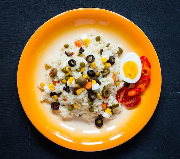 Salada fresca vegetariana com arroz branco na mesa de madeira