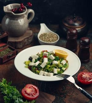Salada gree com cubos de queijo branco e limão.