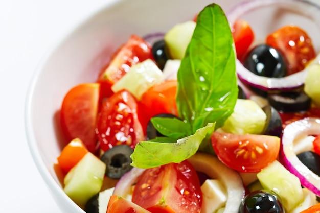 Salada grega clara com legumes frescos, decorada com manjericão.