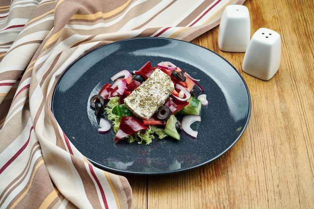 Salada grega clássica com tomates, cebolas, pepino, queijo feta e azeitonas pretas em chapa preta na madeira.