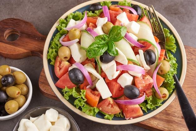 Salada grega clássica de vegetais frescos, pepino, tomate, pimentão, alface, cebola roxa, queijo feta e azeitonas com azeite. comida saudável, vista de cima