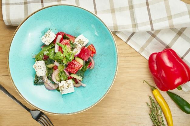 Salada grega com azeitonas, tomate, queijo feta, cebola em uma tigela azul na mesa de madeira. fechar-se. foco seletivo