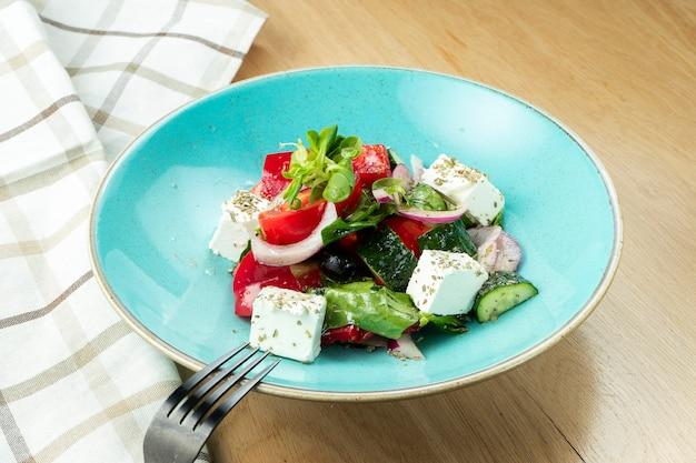 Salada grega com azeitonas, tomate, queijo feta, cebola em uma tigela azul na parede de madeira. fechar-se. foco seletivo