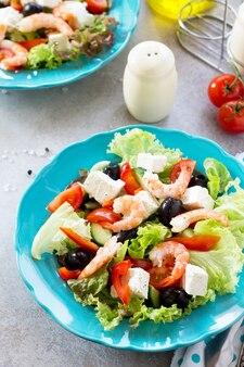 Salada grega com camarões e vegetais em uma mesa leve de pedra ou ardósia