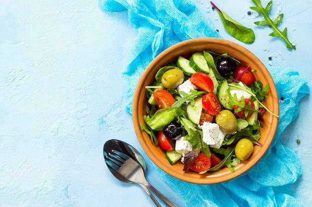 Salada grega com legumes frescos, queijo feta e azeitonas pretas em uma pedra azul ou mesa de concreto copiar espaço vista superior superfície plana
