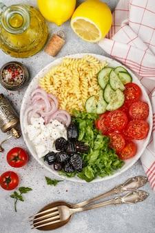 Salada grega com pasta fusilli, alface, tomate, pepino, queijo feta, cebola roxa e azeitonas pretas
