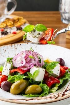Salada grega com queijo feta, azeitonas e ervas, servida em prato branco sobre a mesa de restaurante.
