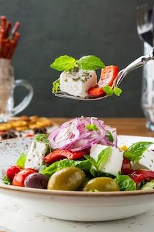 Salada grega com queijo feta, azeitonas e ervas, servidas em um prato branco sobre uma mesa em um restaurante