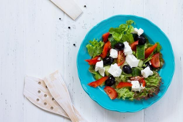 Salada grega com queijo feta de vegetais frescos e azeitonas pretas em um prato azul copie o espaço