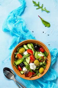 Salada grega com queijo feta de vegetais frescos e azeitonas pretas em uma mesa de pedra azul ou de concreto