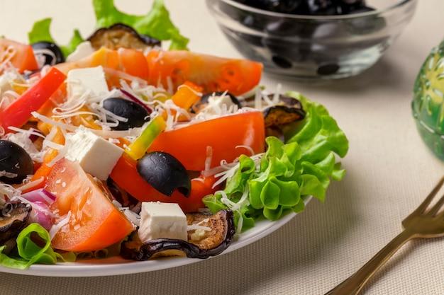 Salada grega com queijo feta, tomate, alface e close-up de azeitonas pretas secas ao sol.