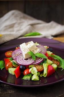 Salada grega com tomate fresco, pepino, cebola roxa, manjericão, alface, queijo feta, azeitonas pretas e ervas italianas no prato.