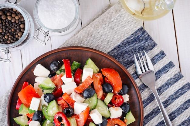 Salada grega com tomate, queijo feta e azeitonas em uma madeira