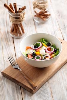 Salada grega de legumes frescos em uma tigela branca na placa de madeira