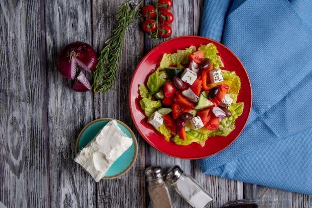 Salada grega de pepino fresco, tomate, pimentão, alface, cebola roxa, queijo feta e azeitonas com azeite de oliva na madeira. comida saudável